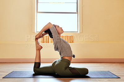 Buy stock photo Shot of a young woman practicing an advanced yoga position