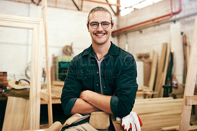 Buy stock photo Portrait of a handsome young carpenter posing with his arms folded inside his workshop