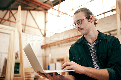 Buy stock photo Cropped shot of a handsome young carpenter using a laptop while working inside his workshop