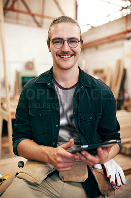 Buy stock photo Portrait of a handsome young carpenter using a digital tablet while working inside his workshop