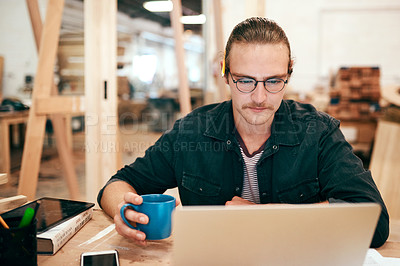 Buy stock photo Cropped shot of a handsome young carpenter drinking coffee and working on a laptop inside his workshop