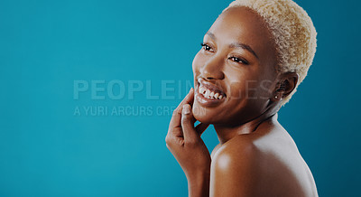 Buy stock photo Cropped shot of a beautiful young woman posing against a blue background