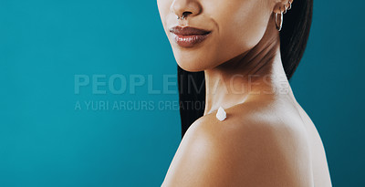 Buy stock photo Cropped shot of a beautiful young woman applying moisturizer to her skin