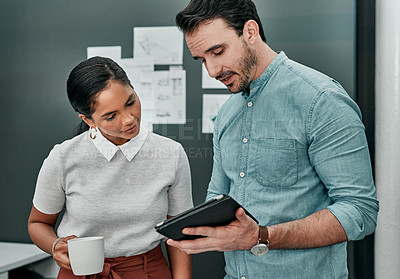 Buy stock photo Shot of two architects working together on a digital tablet in an office