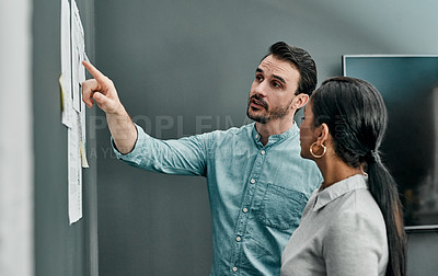 Buy stock photo Shot of two architects working with blueprints on a wall in an office