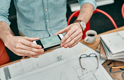 Buy stock photo Closeup shot of an unrecognisable architect using a cellphone to take photos of blueprints in an office
