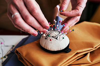 Buy stock photo cropped shot of an unrecognizable designer using a pincushion while working in her workshop