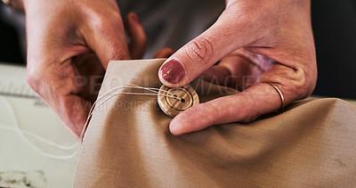 Buy stock photo Cropped shot of an unrecognizable woman sewing a button onto a garment
