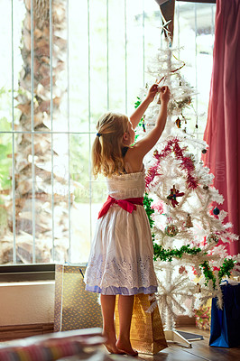 Buy stock photo Full length shot of an adorable little girl decorating a Christmas tree at home