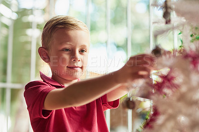 Buy stock photo Shot of an adorable little boy decorating a Christmas tree at home