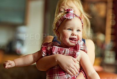 Buy stock photo Shot of an adorable baby girl playing with her older sister at home