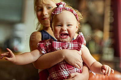Buy stock photo Portrait of an adorable baby girl playing with her older sister at home