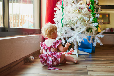 Buy stock photo Rearview shot of an adorable baby girl sitting down and playing in front of a Christmas tree at home