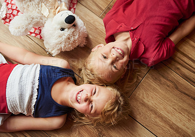 Buy stock photo High angle shot of two adorable young siblings lying down on the floor with their teddy bear at home