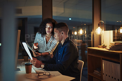 Buy stock photo Shot of a young businessman and businesswoman going through paperwork during a late night at work