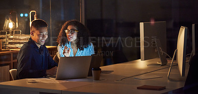 Buy stock photo Shot of a young businessman and businesswoman using a laptop during a late night at work