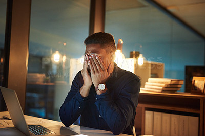 Buy stock photo Shot of a young businessman looking stressed out during a late night at work