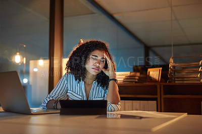 Buy stock photo Shot of a young businesswoman looking stressed out during a late night at work