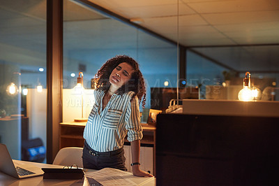 Buy stock photo Shot of a young businesswoman experiencing back pain during a late night at work