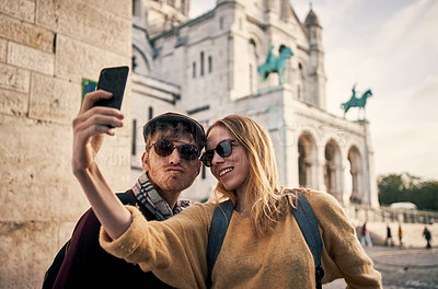Buy stock photo Cropped shot of a happy young couple standing together and taking a selfie with a cellphone while sightseeing Paris