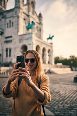 Buy stock photo Cropped shot of an attractive young woman standing alone and taking a selfie with a cellphone while sightseeing Paris