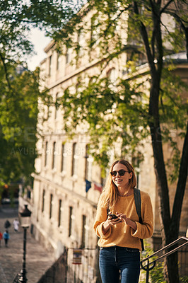 Buy stock photo Cropped shot of an attractive young woman standing alone and using her cellphone while sightseeing in Paris
