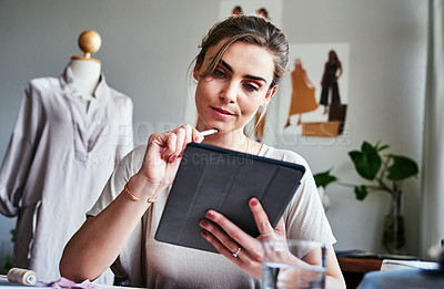 Buy stock photo Cropped shot of a fashion designer using a digital tablet while sitting in her workshop