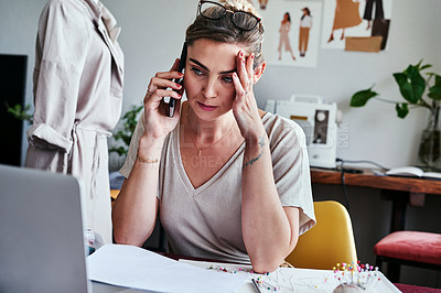 Buy stock photo Shot of a young designer looking stressed while talking on her cellphone
