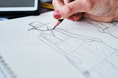 Buy stock photo Cropped shot of a fashion designer working on new sketches at her desk
