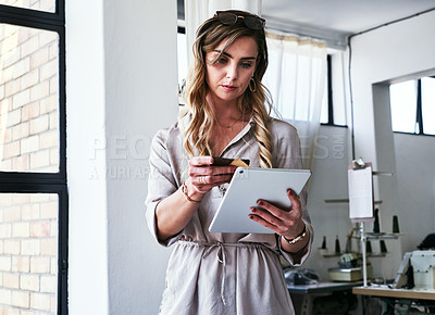 Buy stock photo Cropped shot of a young designer using a digital tablet  at work