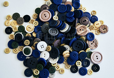 Buy stock photo Shot of sewing buttons laying on a white background