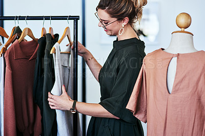 Buy stock photo Cropped shot of a designer looking at garments on a railing in her workshop