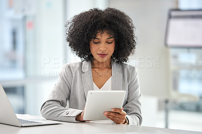 Buy stock photo Cropped shot of an attractive young woman using a digital tablet while working inside her office