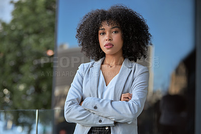 Buy stock photo Portrait of an attractive young businesswoman posing with her arms folded outside her office building