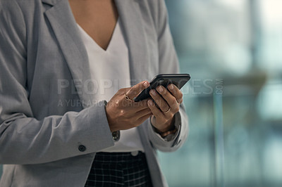 Buy stock photo Cropped shot of an unrecognizable businesswoman using a cellphone while working inside her office