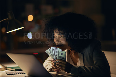 Buy stock photo Cropped shot of an attractive young businesswoman holding a stack of banknotes while working inside her office at night