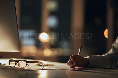 Buy stock photo Cropped shot of an unrecognizable businesswoman writing notes on her diary while working inside her office at night