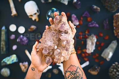 Buy stock photo Closeup of an unrecognizable person holding a crystal with two hands over a table filled with more crystals inside during the day