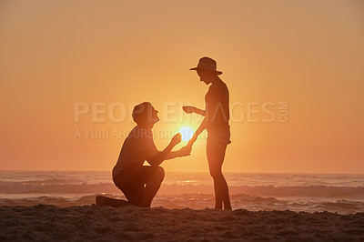 Buy stock photo Shot of a happy young couple getting engaged on the beach at sunset