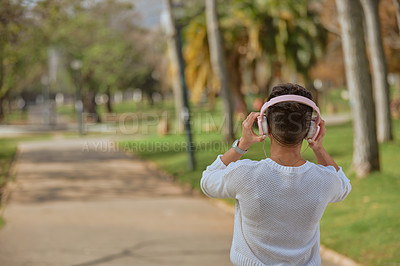 Buy stock photo Rearview shot of a young woman listening to music with headphones in the park