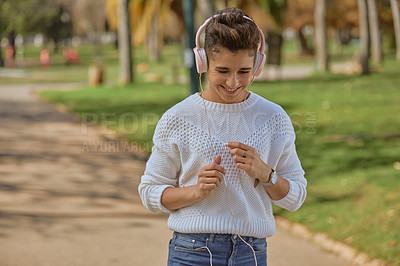Buy stock photo Shot of a happy young woman listening to music and dancing in the park