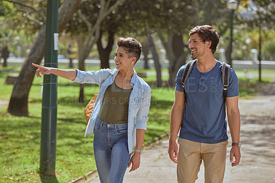 Buy stock photo Shot of a young couple going for a romantic walk in the park