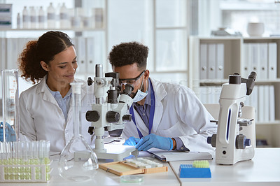 Buy stock photo Shot of two young scientists using a microscope in a lab