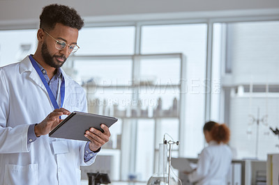 Buy stock photo Shot of a young scientist using a digital tablet in a lab with a colleague in the background