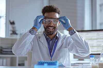 Buy stock photo Shot of a young scientist putting on safety goggles in a lab