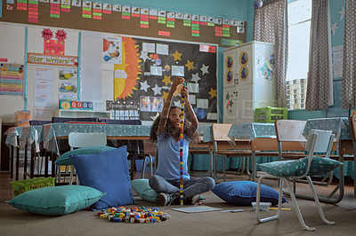 Buy stock photo Shot of a young girl playing with building blocks at school