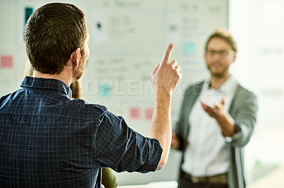 Buy stock photo Cropped shot of an unrecognizable businessman standing and raising his hand to ask his colleague a question in the office