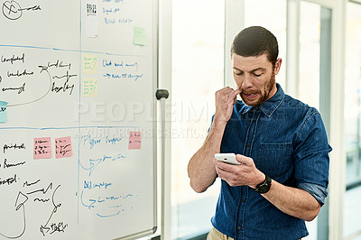 Buy stock photo Cropped shot of a handsome young businessman standing alone and using his cellphone in the office