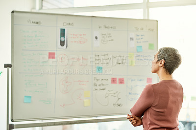 Buy stock photo Cropped shot of an attractive mature businesswoman standing alone and using a white board in the office to strategise