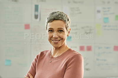 Buy stock photo Cropped shot of an attractive mature businesswoman standing alone with her arms folded in the office